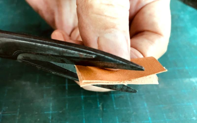 cutting out petal shape from leather piece